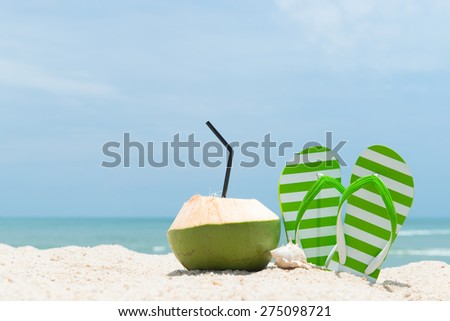 Pair of green striped sandal and coconut drink on the beach - stock photo