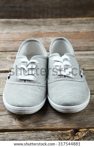 Pair of grey shoes on wooden background
