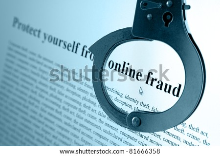 Pair of handcuffs frame the words online fraud on a computer monitor - stock photo