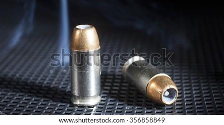 Pair of handgun cartridges on black with smoke behind - stock photo