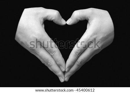 pair of hands in the form of heart on a black background - stock photo
