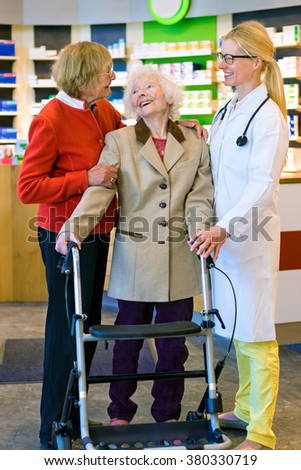 Pair of happy elderly women enjoying a conversation with female doctor in white lab coat in front of pharmacy counter