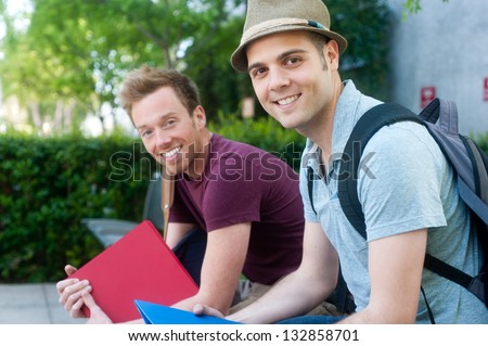 pair of happy young male students on campus - stock photo