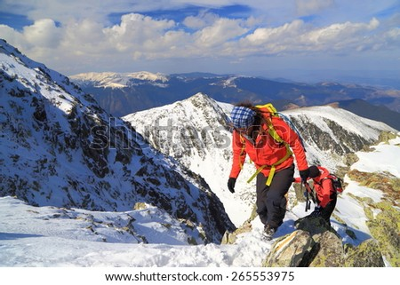 Pair of hikers climbing on snowy path above the mountains - stock photo