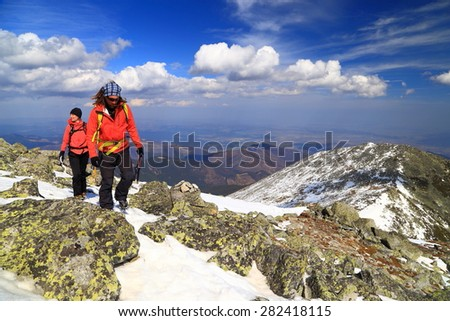 Pair of hikers follow a sunny trail on top of snow covered mountains - stock photo