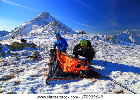 Pair of hikers pitching a tent on snowy mountain - stock photo