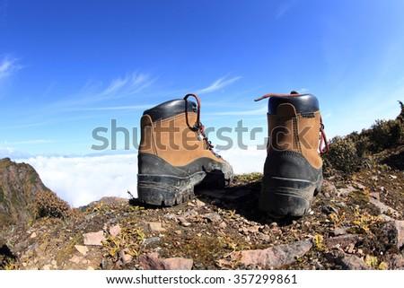 pair of hiking boots on beautiful mountain peak - stock photo