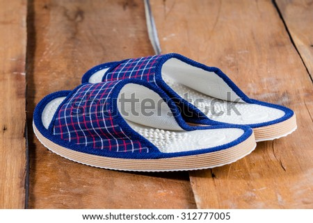 Pair of house slippers on wooden floor - stock photo