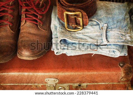 Pair of jeans, shoes, belt on a vintage suitcase - stock photo