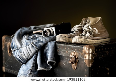 Pair of jeans sneakers and old movie camera on a vintage suitcase - stock photo