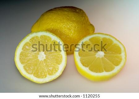 pair of lemons isolated on multi-shaded background for drama. - stock photo