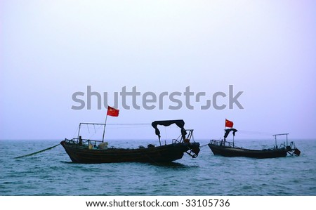 pair of little fishing boats with chinese flags on Yellow sea - stock photo