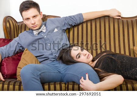 Pair of lovers in living playing. Persons in luxury home interior. Attractive couple at ancient room sitting on couch or sofa. Portrait of handsome fashionable man with charming woman posing indoor. - stock photo