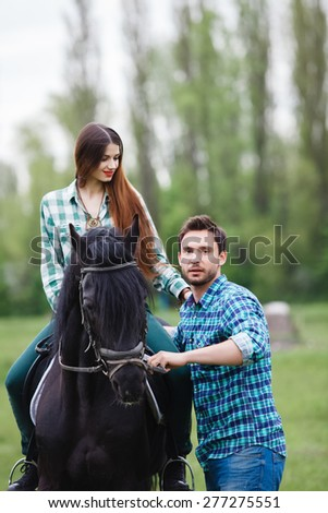 pair of lovers walk with a horse - stock photo