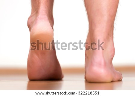 Pair of male feet stepping - view from back. - stock photo