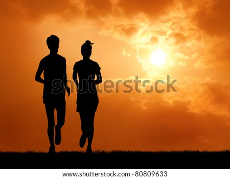 pair of man and woman runner at sunrise silhouetted - stock photo