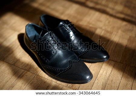 pair of men's black leather ankle shoes placed on wooden floor.
