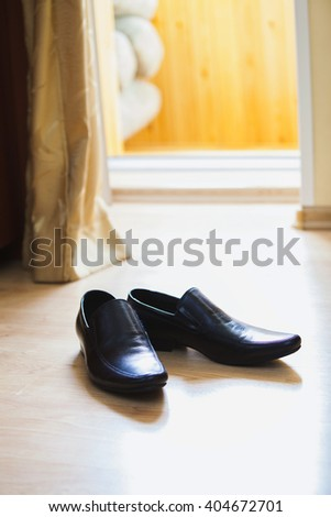 pair of men's black leather ankle shoes placed on wooden floor. - stock photo