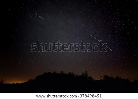 Pair of Meteors. Meteor Shower Night Sky Landscape Silhouette. Shooting Stars - stock photo