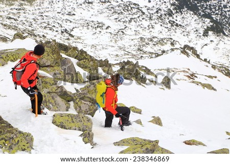Pair of mountain climbers on snow covered slope during winter - stock photo