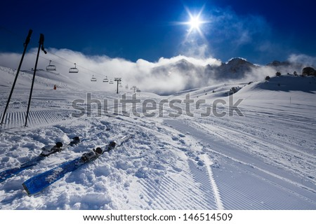 Pair of mountain skies and fresh morning slope with clouds on mountains on background - stock photo