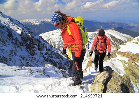 Pair of mountaineers climb a steep ridge on snow covered mountain