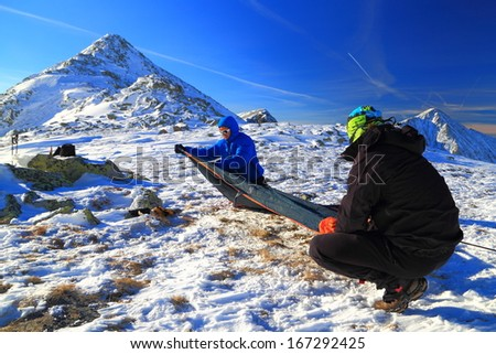 Pair of mountaineers pitching a tent on snowy mountain - stock photo