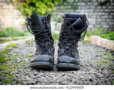 Pair of old army boots on stones surface, shallow depth of field - stock photo