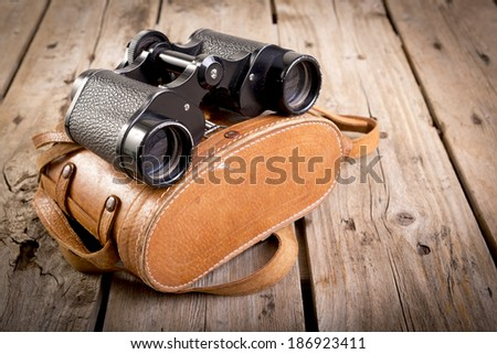 Pair of old binoculars with vintage leather strap and case on a rough wooden surface - stock photo