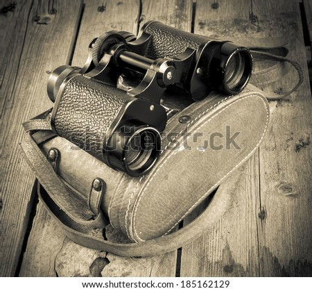 Pair of old binoculars with vintage leather strap and case on a rough wooden surface filtered - stock photo