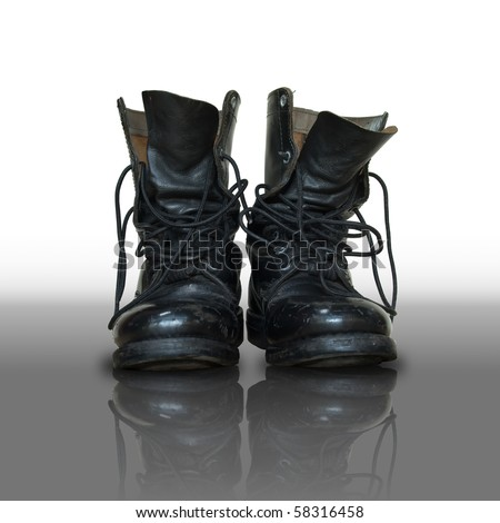 pair of old black combat on reflect floor - stock photo