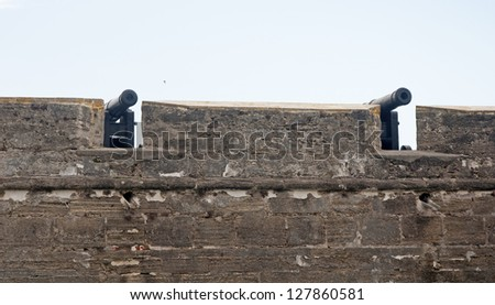 Pair of old canons behind the fort walls, aiming at the sea, on an overcast day. Castillo de San Marcos, St. Augustine, Florida. 16th century. - stock photo