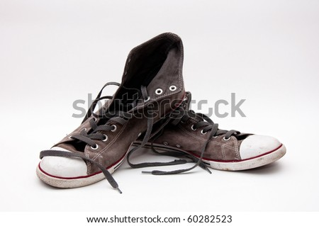 pair of old dirty gray sneakers - stock photo