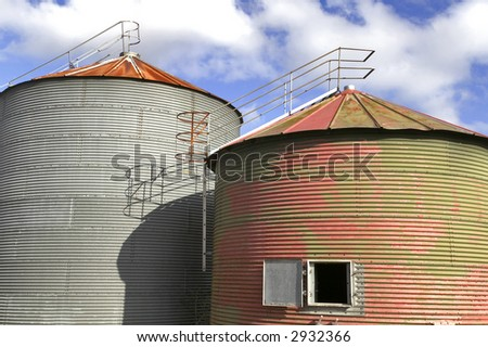 Pair of old grain drying silo's against a blue cloudy sky - stock photo