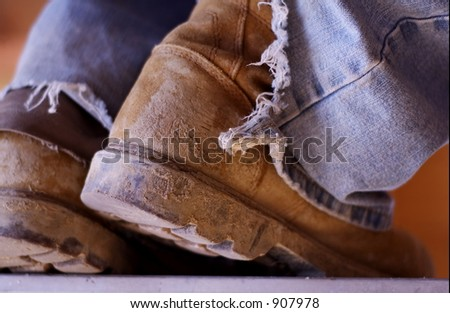 pair of old muddy construction boots on laborer
