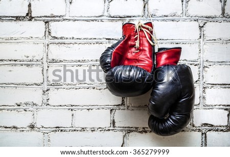 Pair of old red and black boxing gloves hanging on white brick wall. - stock photo