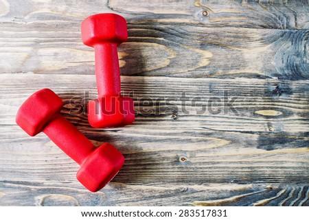 Pair of orange 3 kg dumbbells on wooden rustic background - stock photo