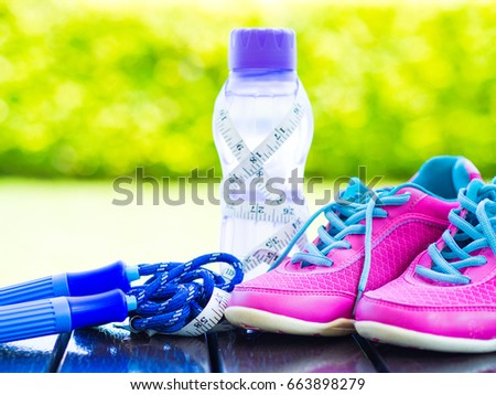 Pair of pink sport shoes towel water bottle and Jump rope on wooden board. In the background forest or park trail. Accessories for running sport.