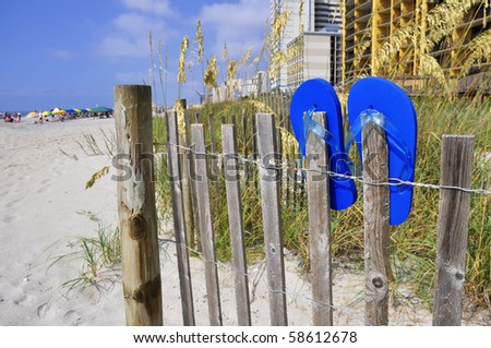 Pair of pretty blue flip flop sandals stuck on a beach fence - stock photo