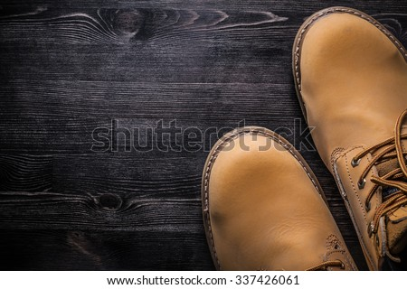 Pair of protective working boots on wood board construction concept.