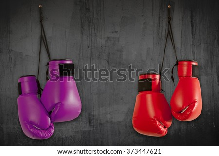 Pair of purple boxing gloves hanging on wall - stock photo