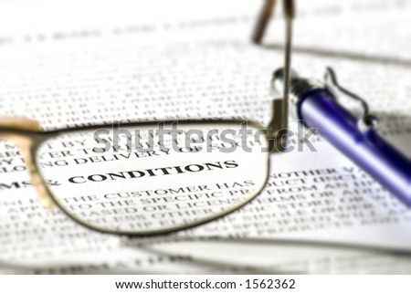Pair of reading glasses on paper with word 'conditions' in focus - stock photo