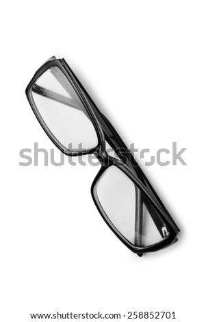 Pair of reading glasses or spectacles with modern dark frames folded up on a white background, view from above - stock photo