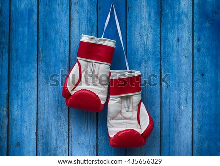 pair of red boxing gloves hanging on the old blue wooden wall - stock photo