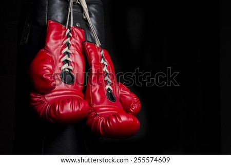 Pair of red boxing gloves with low key lighting - stock photo
