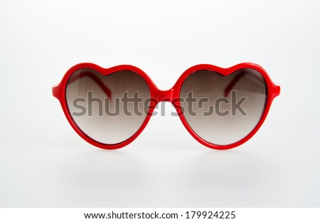 Pair of Red Heart Shaped Sunglasses on White Background - stock photo