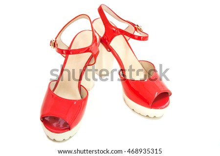 Pair of red womens high heeled patent shoes on white background.