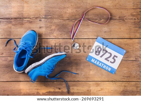 Pair of running shoes, medal and race number on a wooden floor background - stock photo