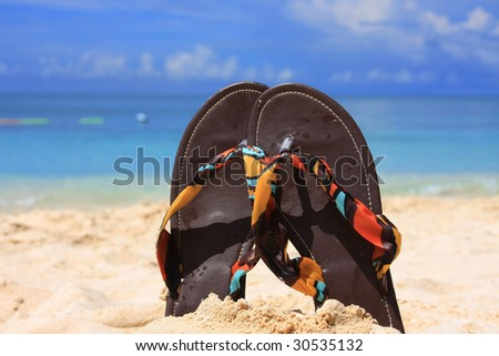Pair of sandals in sand on island beach resort - stock photo