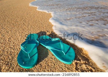 pair of sandals just about to be washed away by the sea on the beach - stock photo